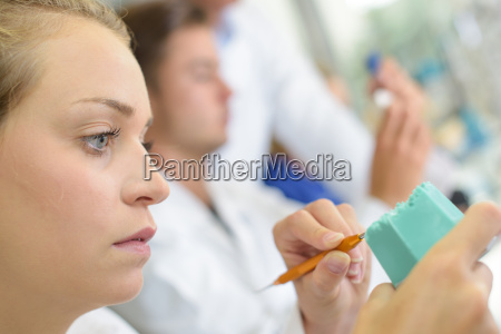 female technician shaping dental impressions