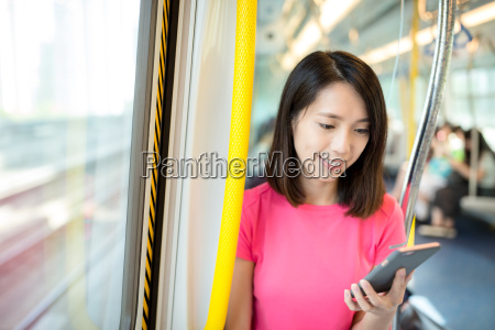 woman use of phone at train
