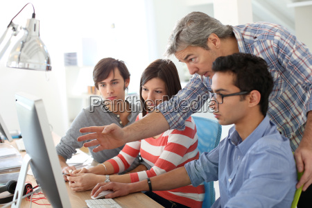 teacher with students working on desktop