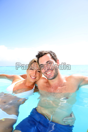 cheerful couple swimming in infinity pool