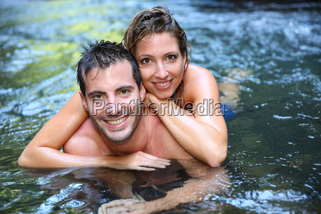cheerful couple bathing in river waters