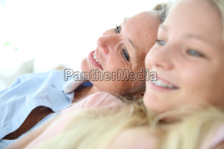 mother and daughter relaxing in sofa