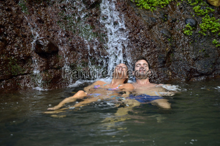 couple enjoying bath under waterfalls