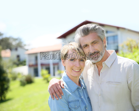 par staende foran nyligt ejet hus