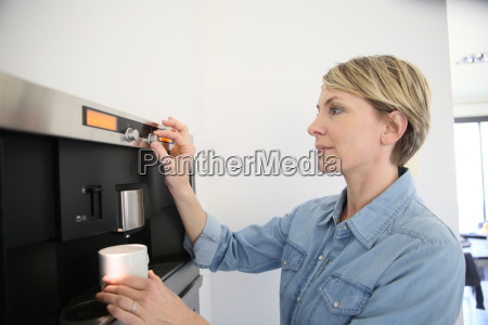 middle aged woman using expresso coffee