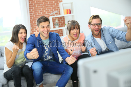 cheerful group of friends watching football