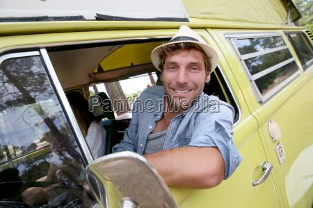 trendy guy riding a vintage camper