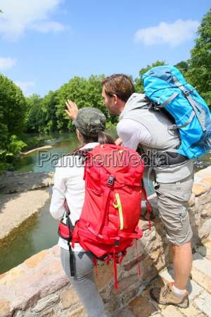 hikers looking at river from stone