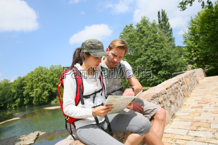 couple of backpackers reading map sit