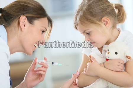 brave little girl receiving injection in