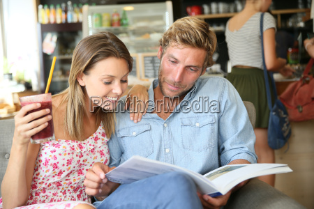 trendy couple in coffee shop reading