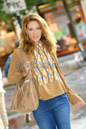 trendy girl walking in shopping street
