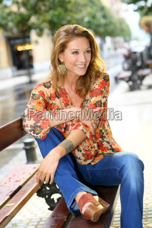 attractive trendy woman sitting on public