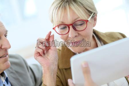 senior woman trying new eyeglasses on