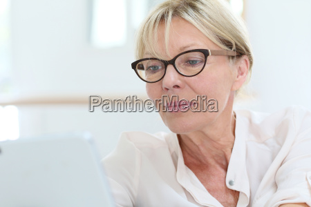 senior woman with eyeglasses connected on