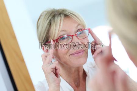 elderly woman trying eyeglasses on in