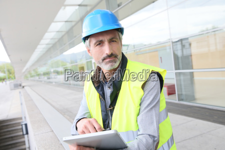 engineer with hard hat using tablet