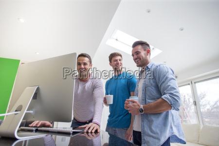 friends gathered around computer