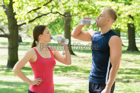 couple drinking water in park