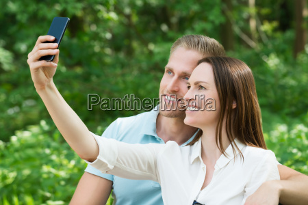 couple taking picture with their smartphone