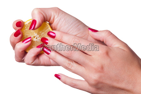 hand crushed lemon with red fingernails