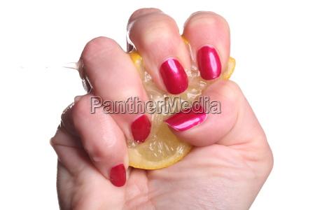hand with red fingernails crushed lemon