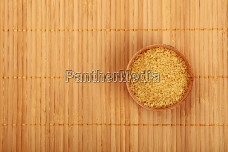 wooden bowl of brown cane sugar