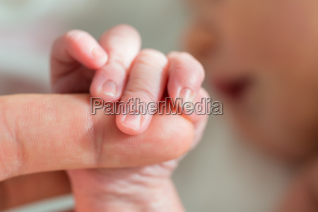 baby holding mothers finger