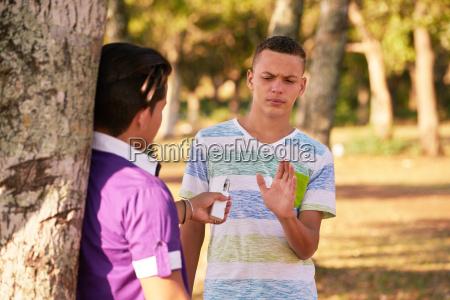 teenagers smoking boy refusing to smoke
