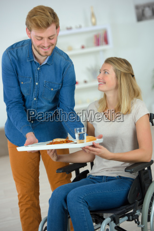 carer giving lunch to you woman