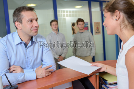 lady handing form to man at
