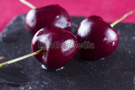 three cherries over black stone