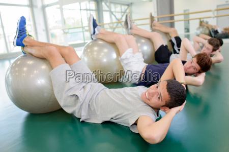 four men with feet on aerobic