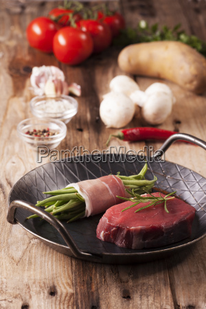 raw steak in an iron pan