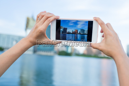 woman taking photo on cellphone in
