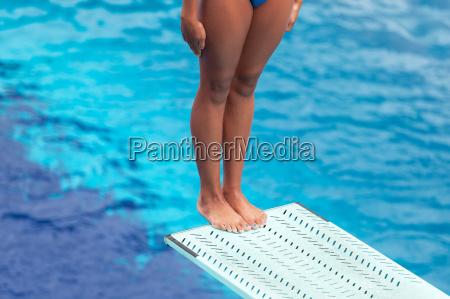 girl standing on a springboard preparing