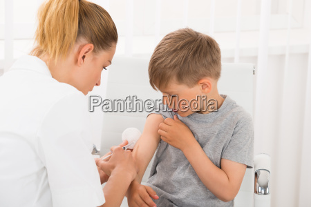 doctor giving an injection to boy