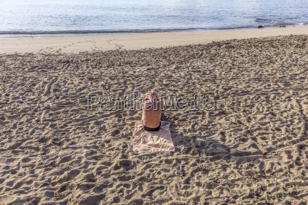 elderly man sitting at the beach