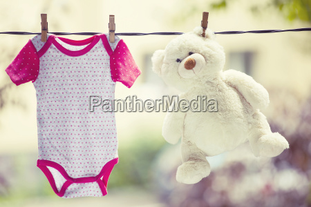 baby clothes and teddy bear hanging