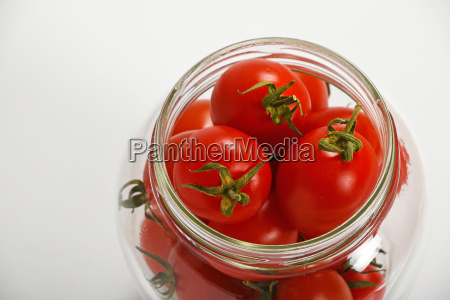cherry tomatoes in glass jar over