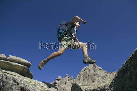spain hiker with backpack jumping on