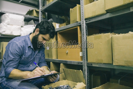 manan examining business inventory writing on