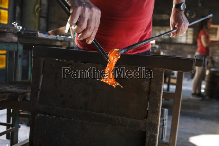 man working with molten glass using