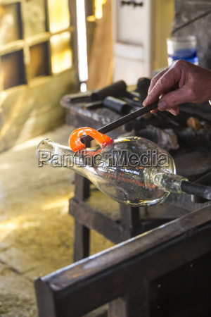 man manufacturing a glass base in