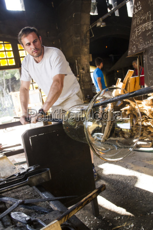 man working with molten glass in