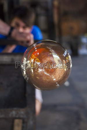 man blowing molten glass with a