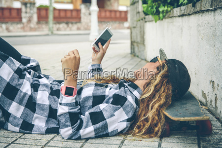 young woman lying on skateboard looking