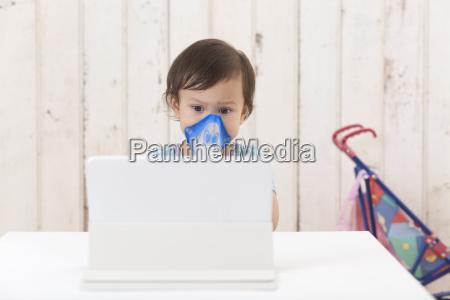 girl using inhaler looking at digital