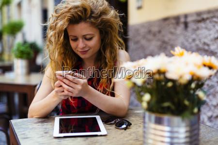 woman at outdoor cafe looking at