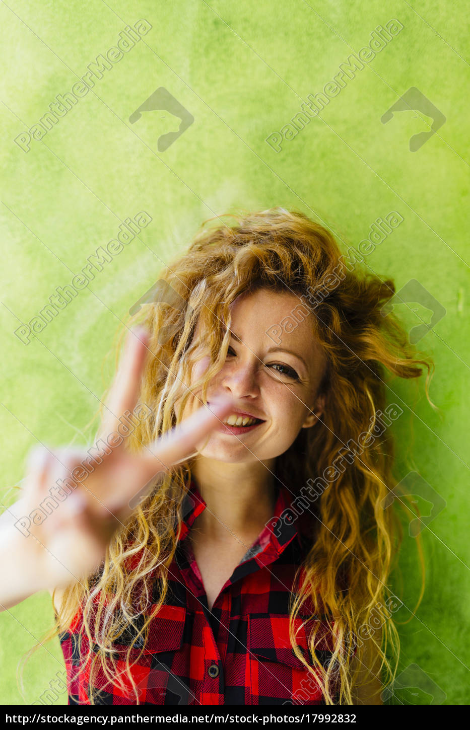 portrait, of, smiling, woman, showing, victory - 17992832